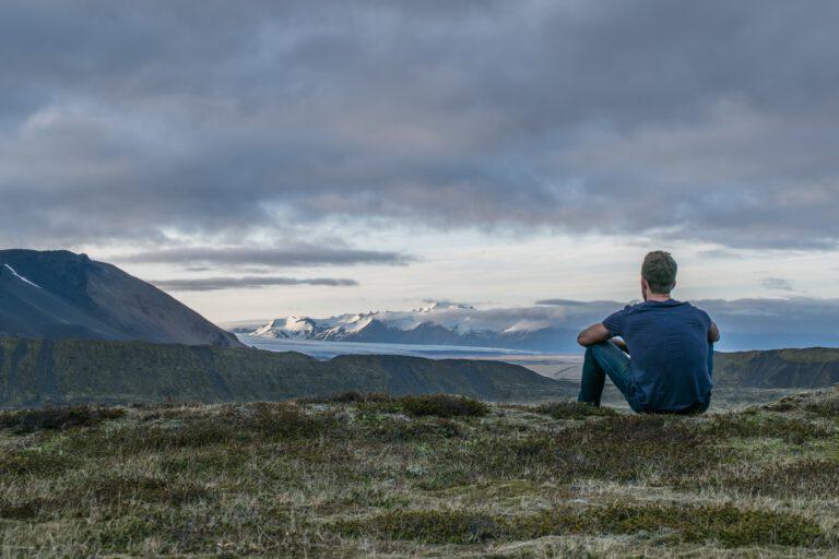 Man kijkt uit over landschap en denkt na over de 5 confronterende vragen over vertrouwen en zelfregie
